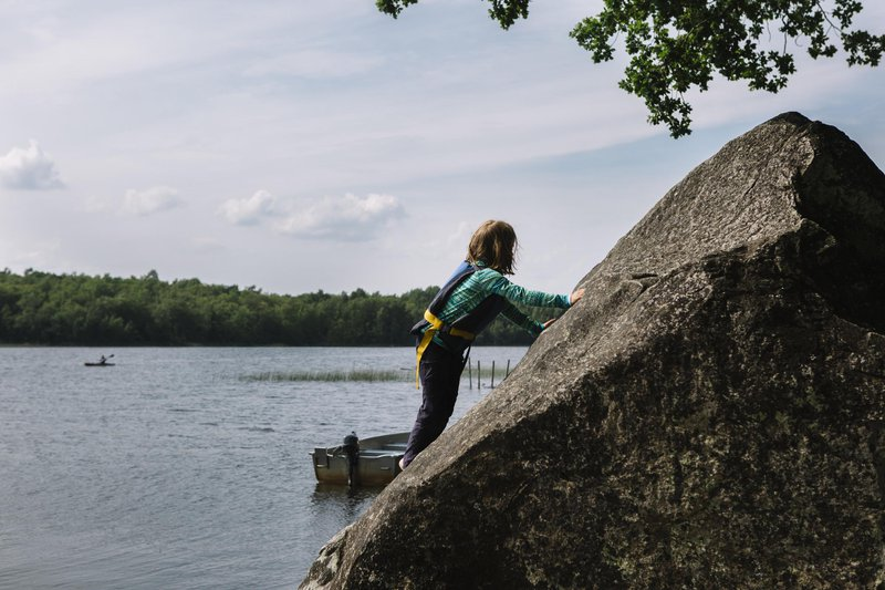 Child climbing a rock by the water, in Småland