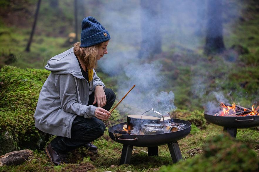 Ein Mädchen, das eine Mütze trägt, kocht im Wald über offenem Feuer.