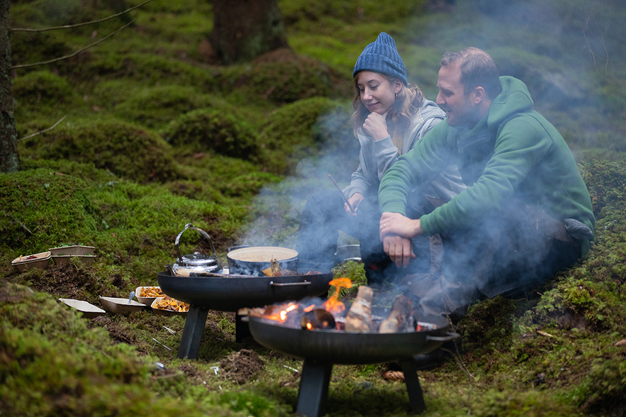 A man and a woman sitting in the forest cooking over open fires. Smoke is billowing.